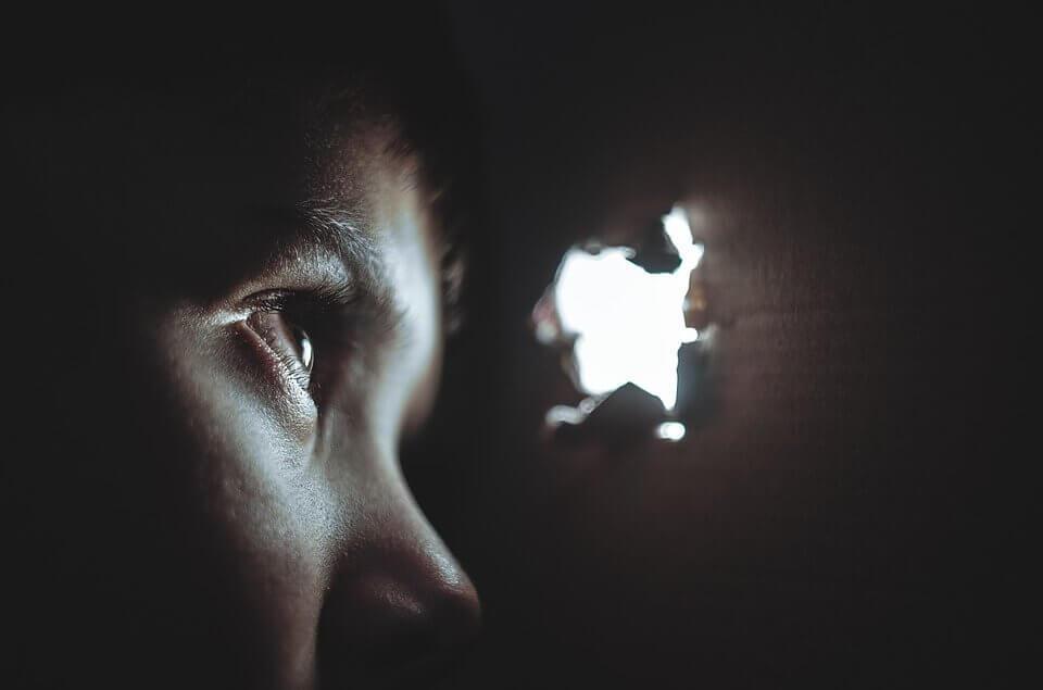 Niño espiando por un agujero