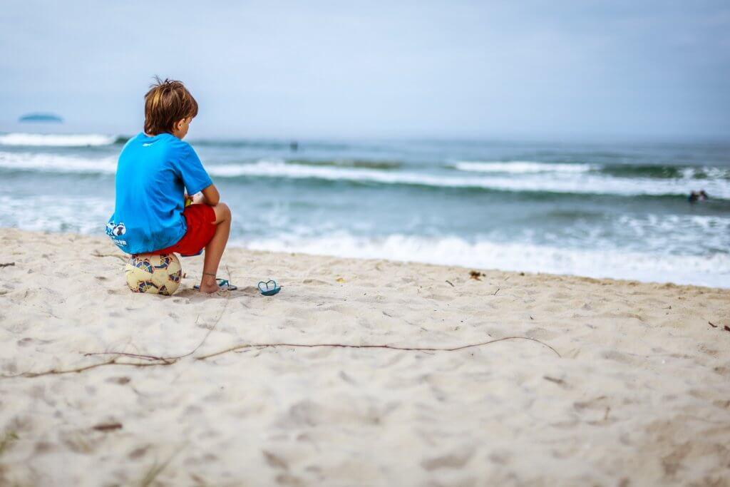 Niño mirando al mar sobre una pelota