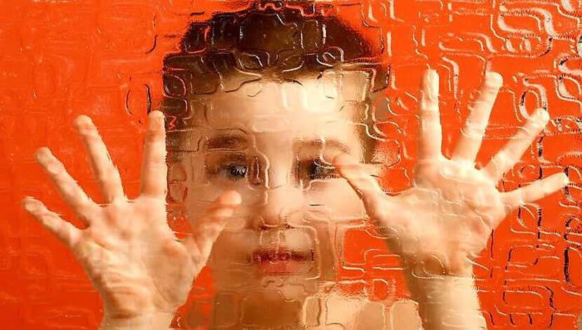 Niño con sus manos sobre un cristal por depresión enmascarada