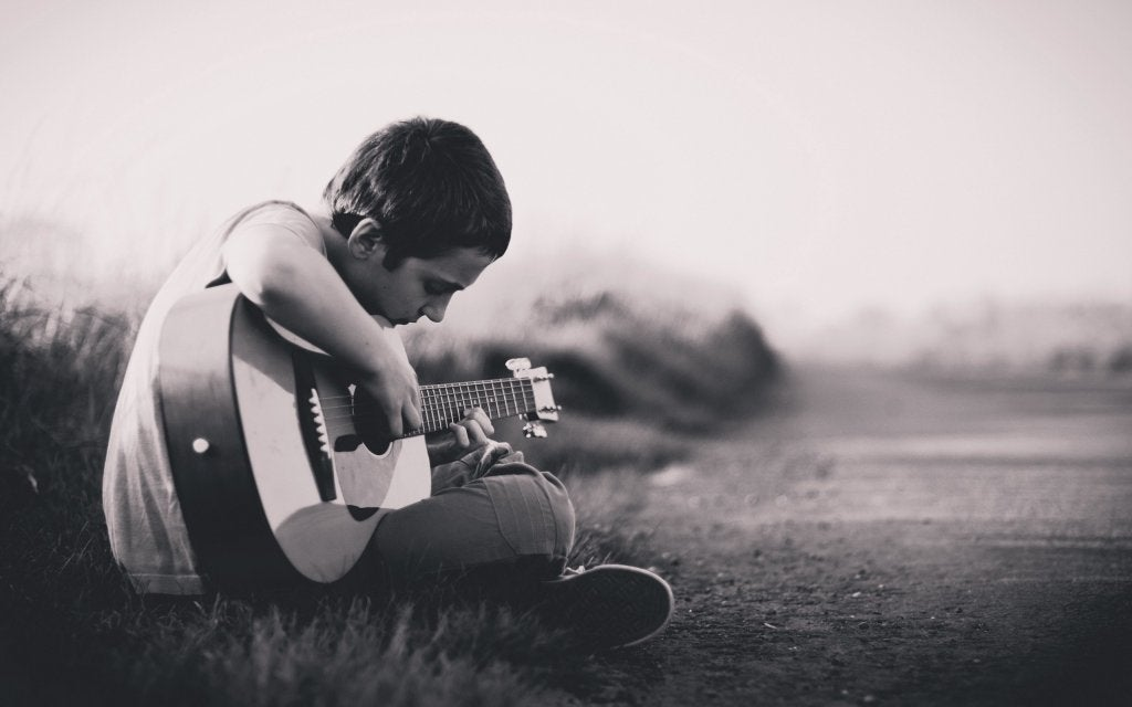 niño desanimado con guitarra