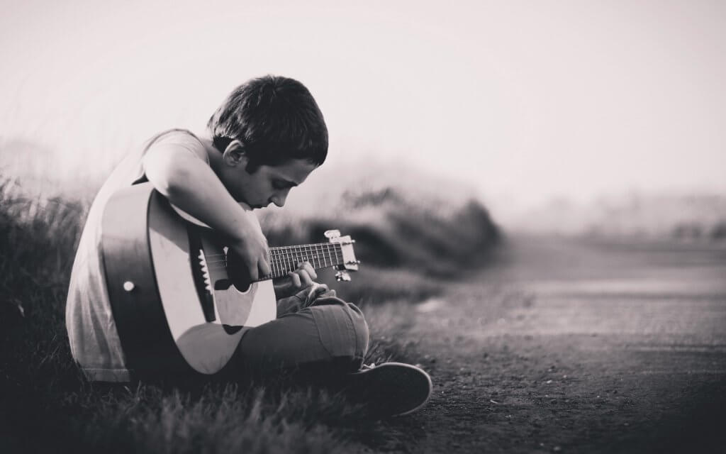 Niño triste tocando la guitarra