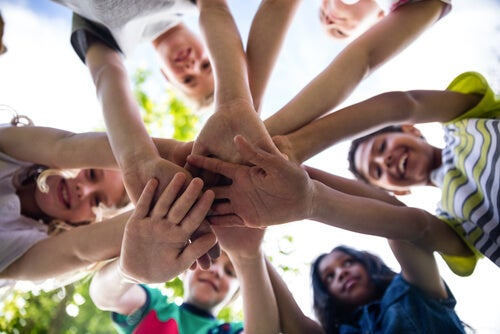 Niños poniendo sus manos juntas