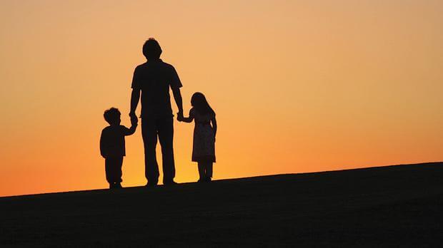 padre al amanecer con sus dos hijos de la mano