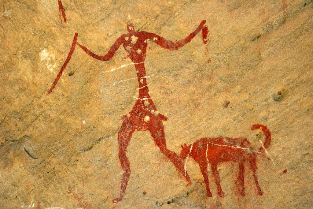 Pintura rupestre de un hombre con sus perros representando la empatía en los perros