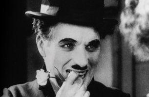Charles Chaplin sonriendo con flor en la boca