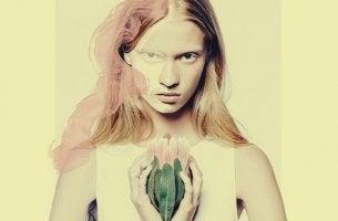 chica con flor entre las manos que piensa lo que haces