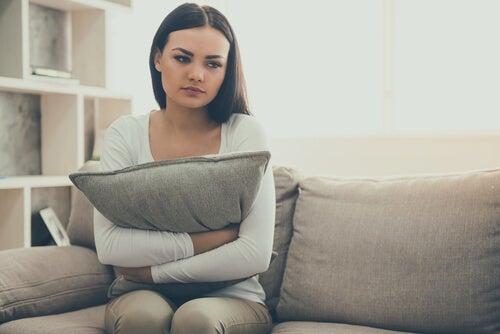 Chica sentada en un sofá pensando excusas para no ir al psicólogo