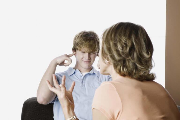 Chico adolescente tapándose los oídos para no escuchar a su madre
