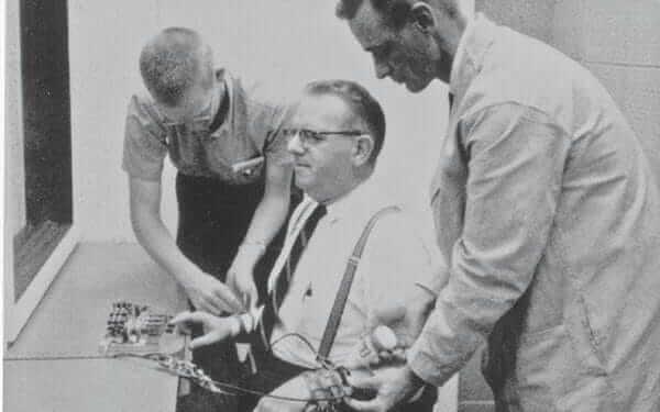 Hombres poniendo aparatos en otro en el experimento de Milgram