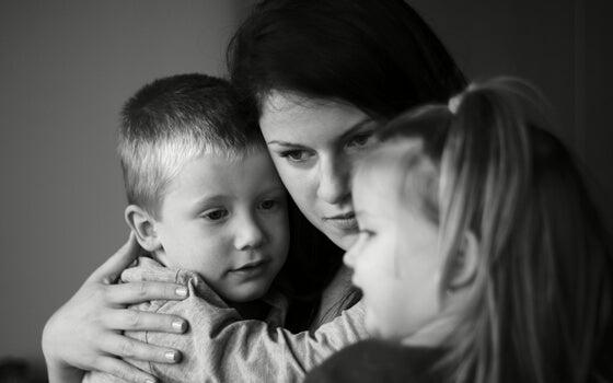 madre abrazada a sus hijos