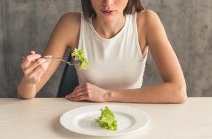 Mujer con ortorexia comiendo lechuga