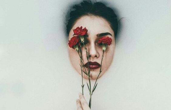 mujer con claveles en el rostro representando la resaca emocional