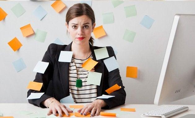 Mujer con estrés crónico rodeada de post-its que piensa en cambiar de trabajo