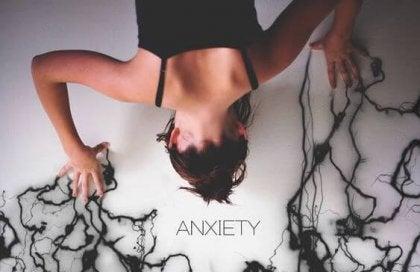 mujer con ansiedad de cuyas manos salen hebras oscuras