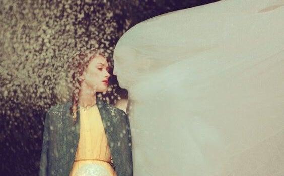 Mujer con hombre cubierto bajo un velo blanco
