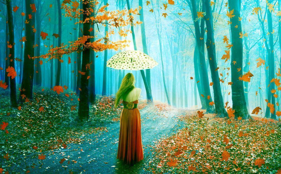 Mujer con paraguas paseando por el bosque pensando en el olvido
