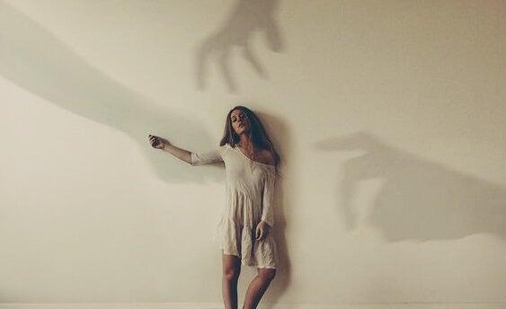 mujer con sombras que señalan su culpa