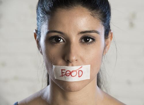 Mujer con un cartel en la boca en el que la palabra comida está tachada