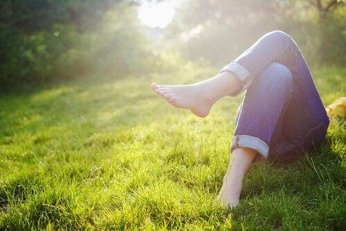 Mujer descalza tumbada en el cesped
