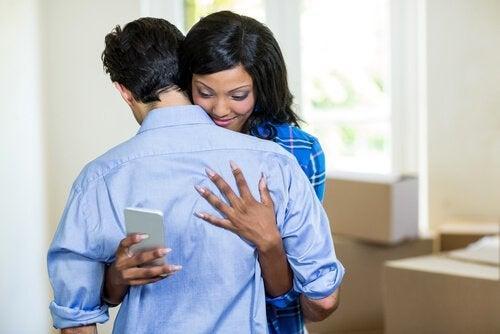 Mujer infiel abrazando a su marido mientras ve el móvil