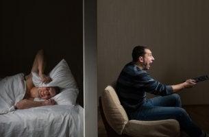 Hombre intentando dormir mientras su vecino hace ruido