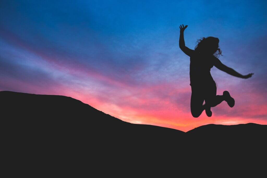Mujer saltando al atardecer