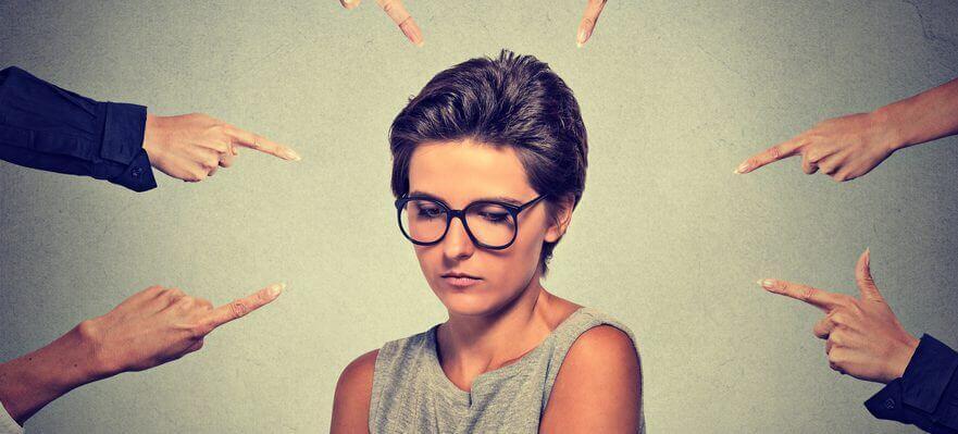 Mujer señalada por sus compañeros de trabajo sufriendo acoso laboral