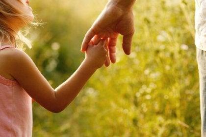 Niña agarrando la mano de su madre mientras le dice gracias papás