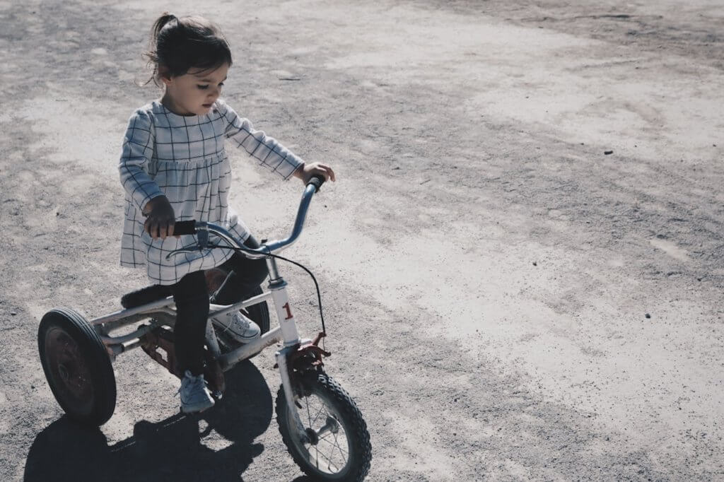 girl riding tricycle helps avoid childhood obesity