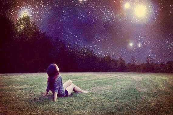 Niña sentada en el césped mirando una estrella