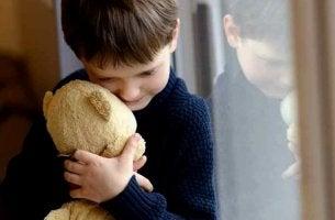 Niño abrazando a un oso sufriendo por vivir con una familia disfuncional