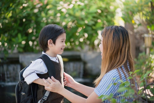 Niño con mochila hablando con su madre sobre el colegio