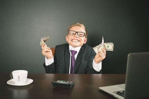 Niño con traje, ordenador y dinero