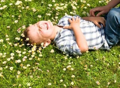 Niño riéndose por las cosquillas que le hacen simbolizando las frases de Gianni Rodari