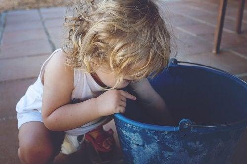 Niño zurdo buscando en un cubo