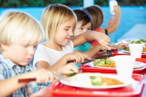 Niños con comida en sus bandejas