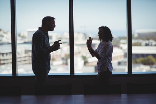Pareja discutiendo cerca de una ventana como ejemplo de lucha de poder en la pareja