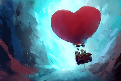 Pareja montada en un globo con forma de corazón