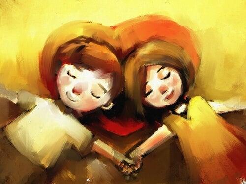 Pareja tumbada sobre un corazón agarrada de la mano