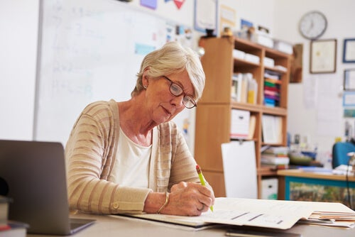 Profesora corrigiendo un examen