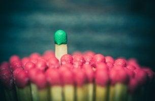 Cerilla verde sobresaliendo sobre un grupo de cerillas rojas como ejemplo del poder social