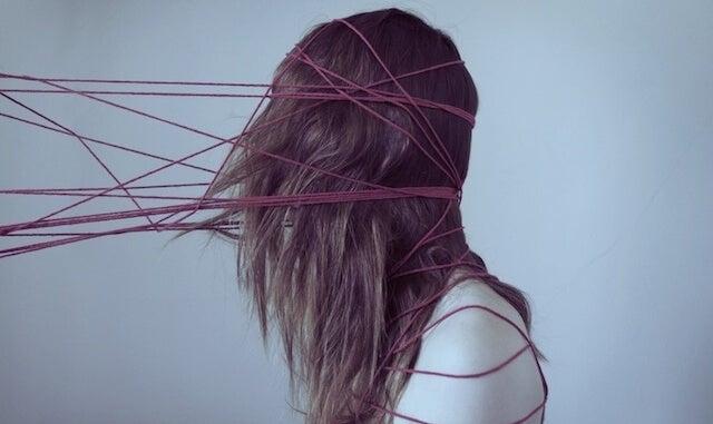 chica atrapada en hilos como efecto de los sesgos cognitivos