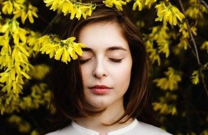 Chica bajo flores amarillas disfrutando de estar bien con uno mismo