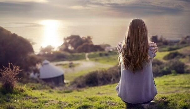Chica de espaldas pensando en la paradoja de la felicidad