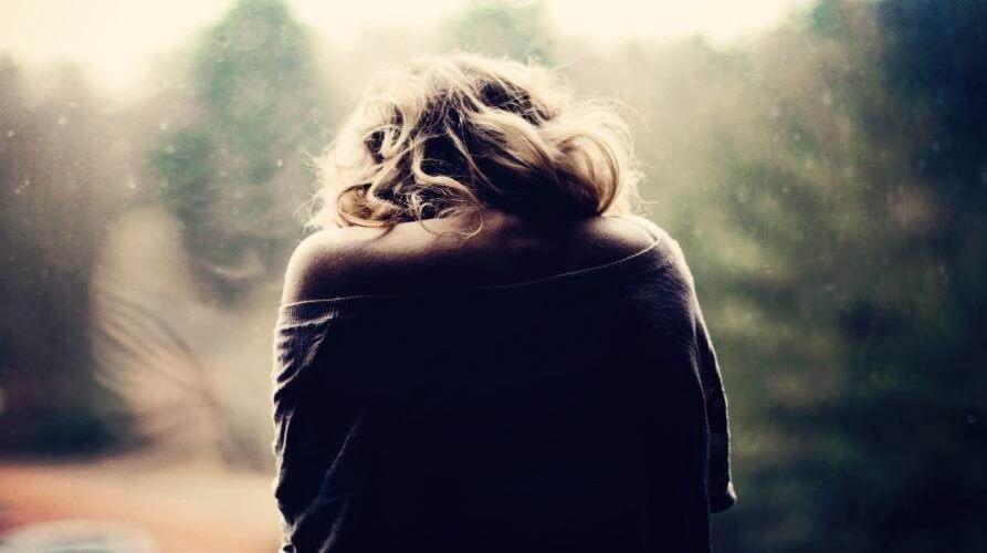Chica de espaldas experimentando tristeza