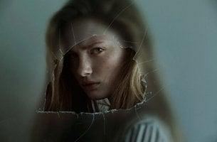 Chica enfadada tras un cristal