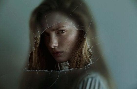 Chica representando la ira enfadada tras un cristal roto