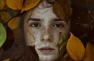 Chico rodeado de hojas