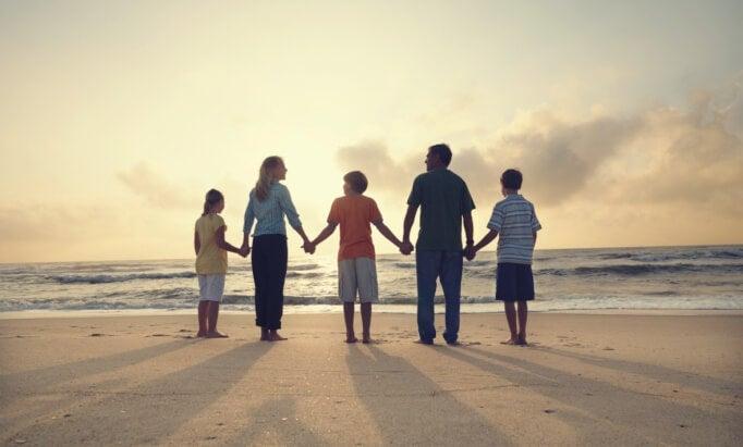 Familia cogida de la mano en la playa