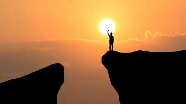 hombre en precipicio tocando sol representando principios de Karl Popper